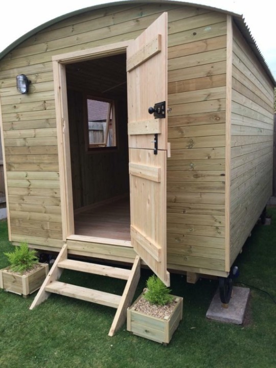 Photo showing off the newly finished shepherd hut's stable door, plants and steps.