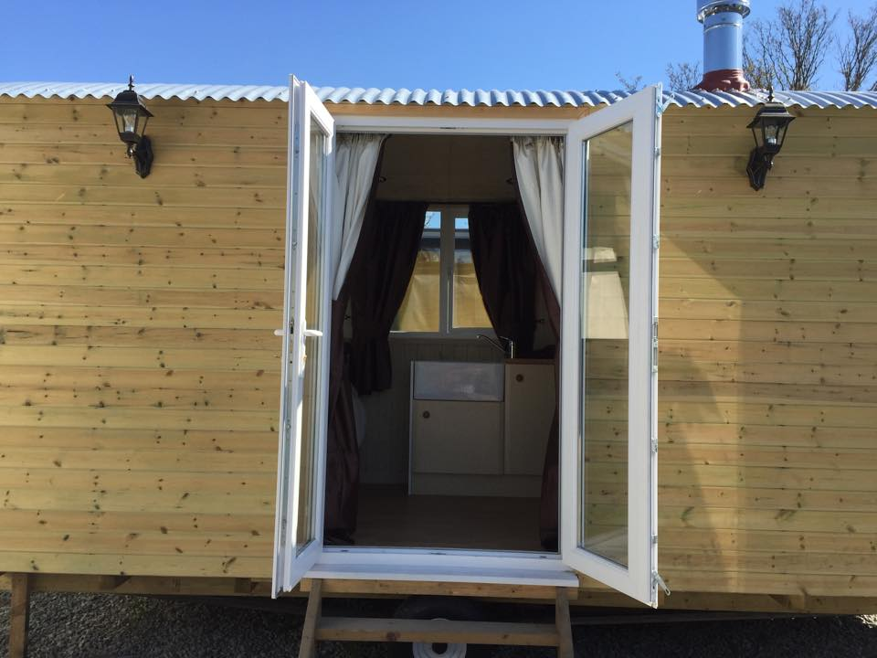Double doors open looking into shepherds hut .